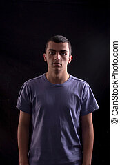 Portret of a serious young man on black background in studio