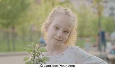 Portret of beautiful smiling girl in the park. Sun and nice nature. Slow motion