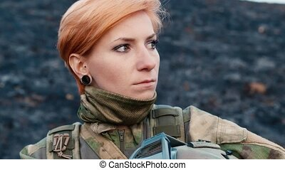 Portret of woman soldier with a weapon
