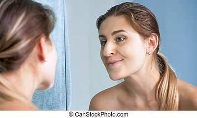 Portriat of beautiful young woman looking at her face in mirror