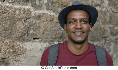 Portriat of happy african tourist man backpacker smiling and looking into camera. Mixed race young guy travelling in Europe