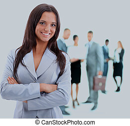 Portrrait of a young business woman with people discussing in background.
