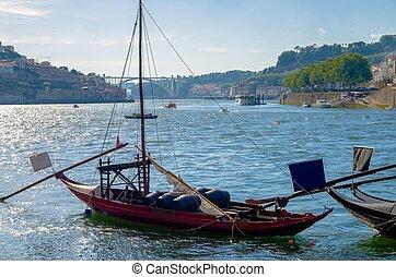 Portugal, Porto, red wooden boat with wine port barrels close up on Douro, Porto by river, Porto in summer, riverbed Douro, Porto city alone the river Douro