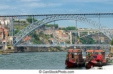 Portugal, Porto, wooden red boats with wine barrels on Douro river close up, wooden boats with port barrels close up on Douro river, Porto old town view, The Eiffel Bridge, Ponte Dom Luis