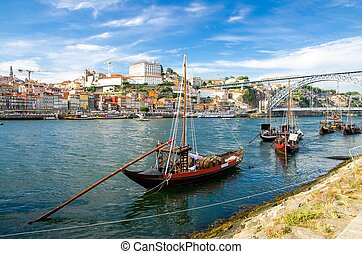 Portugal, city landscape Porto, colored wooden boats with wine port barrels on Douro river, panoramic view of the old town Porto, The Eiffel Bridge view, Ponte Dom Luis, Porto in summer