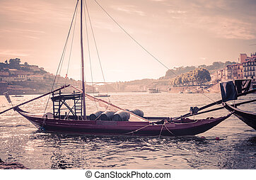 Portugal, old look of Porto , panoramic view of Douro river, red wooden boat with wine port barrels close-up, the banks of the river Douro