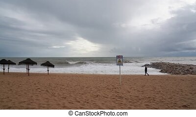 Portuguese beach during a storm, a woman walking along the ...