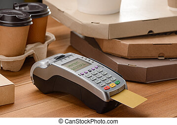 POS terminal with inserted credit card, coffee and pizza