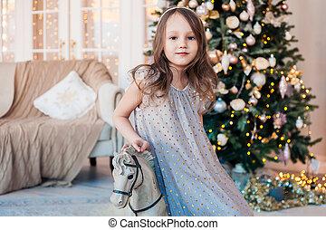 poser, confortable, contre, jolie fille, arbre., intérieur, antiquité, noël, peu, cheval, balancer
