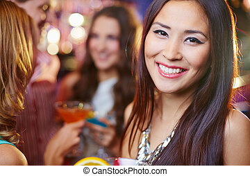 Posh party girl - Joyful Asian girl at a party, her friends...