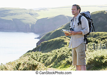 posição homem, ligado, cliffside, caminho, segurando, mapa