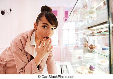 posição mulher, frente, a, vidro, mostruário, com, massas, dentro