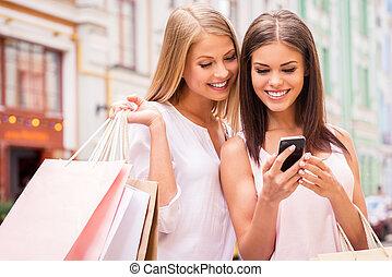 posición, bolsas, compras, móvil, friends., shopaholic, joven, juntos, dos, mirar, teléfono, mientras, atractivo, tenencia, aire libre, mujeres