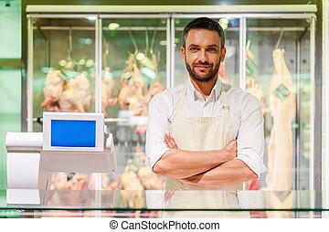 posición, mantener, carne, joven, carnicero, brazos, mirar, confiado, mientras, cámara, cruzado, supermercado, plano de fondo, sonriente, compruebe, butcher.