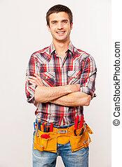 posición, mantener, herramienta, handyman., factótum, gris, contra, joven, alegre, mientras, brazos cruzados, plano de fondo, sonriente, guapo, cinturón