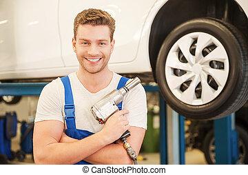 posición, neumático, tenencia, work., coche, joven, confiado, mientras, taller, llave inglesa, plano de fondo, listo, hombre sonriente