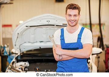 posición, plano de fondo, work., coche, joven, uniforme, confiado, mientras, taller, llave inglesa, tenencia, listo, hombre sonriente, él