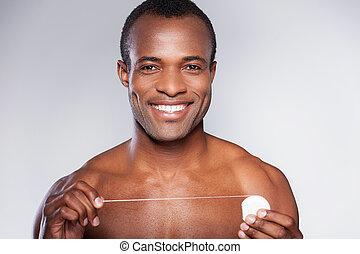 posición, tenencia, joven, dental, africano, gris, contra, floss., mientras, plano de fondo, seda, retrato, sonriente, guapo, shirtless, hombre