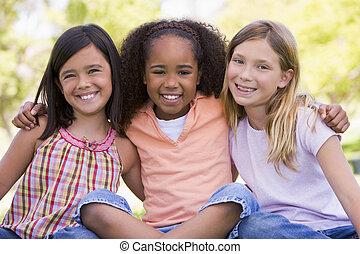 posiedzenie, młody, trzy, outdoors, drużki, uśmiechanie się