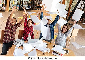 posiedzenie, studenci, paper., do góry, biblioteka, rzucić, szczęśliwy