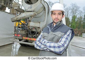 posing behind a mixer truck