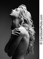 Posing blond woman with long curly hair on black