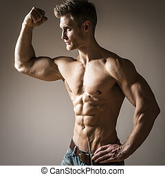Posing young well trained man with perfect abdominam and pectoral muscle