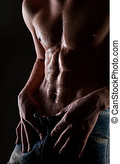 Posing muscular naked man with body in water drops on black