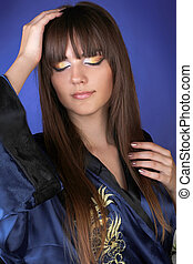 Posing sensual woman with long hair and make up, over blue