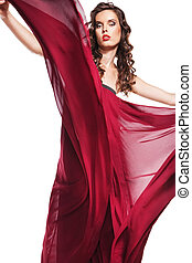Posing woman in red dress flying on wind