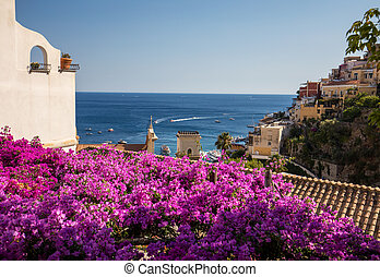 Positano framed by pink bougainvillea and boats in the background. Colourful Positano, the jewel of the Amalfi Coast, with its multicoloured homes and buildings perched on a large hill overlooking the sea. Italy