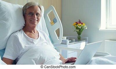 positief, oud, man, het liggen, in het ziekenhuis, bed, met, draagbare computer