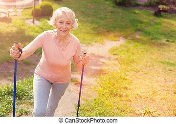 positief, oudere vrouw, wandelende, met, krukken