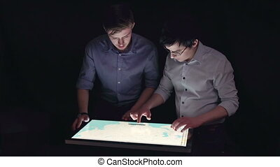 Position Determining - Two men in the dark working with the...