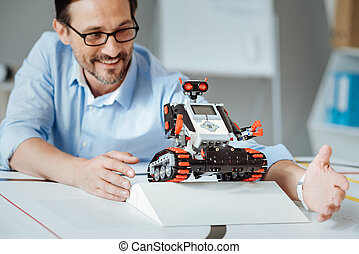 Positive adult engineer testing the robot in a lab
