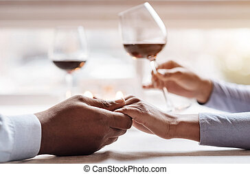 Positive African American couple enjoying the beverage in the restaurant