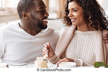 Positive African American couple enjoying the cupcake in the cafe