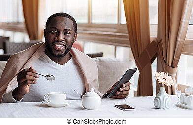 Positive African American man enjoying his breakfast in the cafe