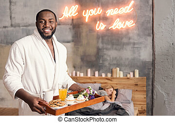 Positive African American man holding breakfast tray in the bedroom