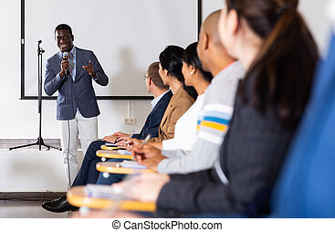 Positive African American with microphone speaking at business event