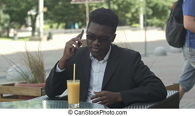 Positive afro american marketing expert in eyewear and casual outfit having phone call in cafe