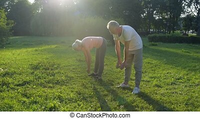 Positive aged couple doing stretching exercises outdoors