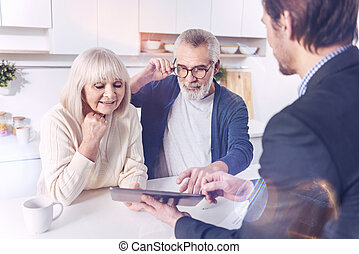 Positive aged couple meeting with their real estate agent