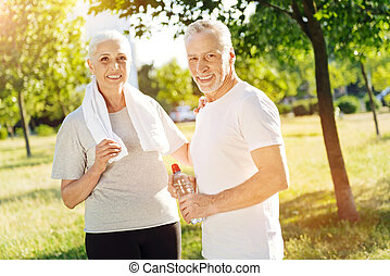 Positive aged couple preparing for sport exercises in the park