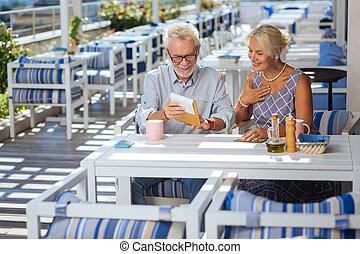 Positive aged couple reading the restaurant menu