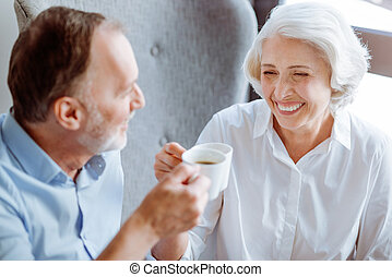 Positive aged couple resting in the cafe