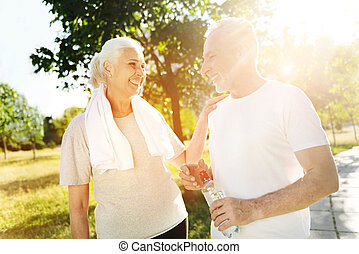 Positive aged couple resting in the park after sport activities