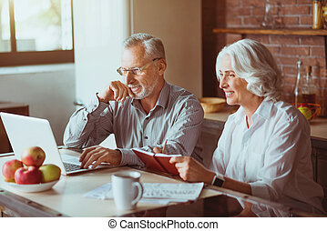 Positive aged couple sitting in the kitchen