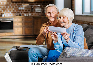 Positive aged couple sitting on the sofa