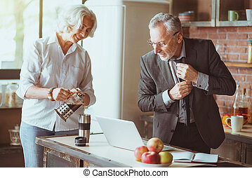 Positive aged couple standing in the kitchen